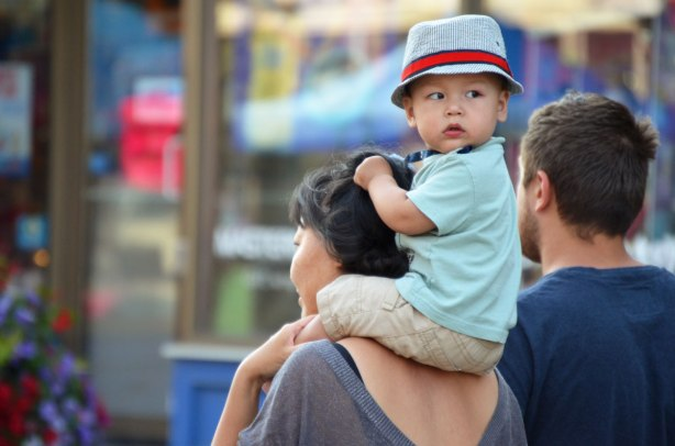 A young Asian boy is on his mother's shoulders.  He is looking back.  He is wearing a greyhat with a red band, as well as a tie.