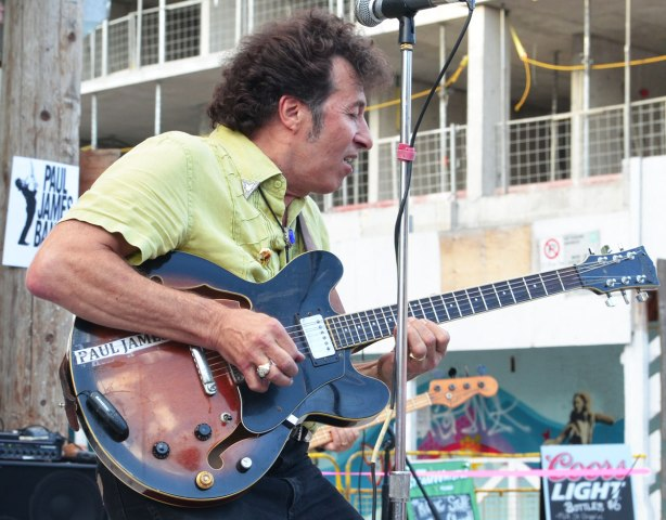 man playing the guitar outdoors at a street music festival