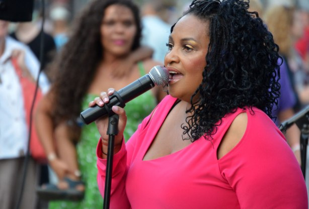 A black woman with shoulder length curly hair and a bright pink top is singing into a microphone. A woman in green is watching her
