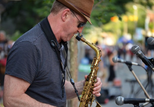 saxophone player playing in front of many microphones at an outdoor music festival