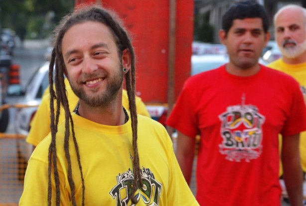 young man in dreadlocks and a yellow Tshirt waiting to perform at a music festival