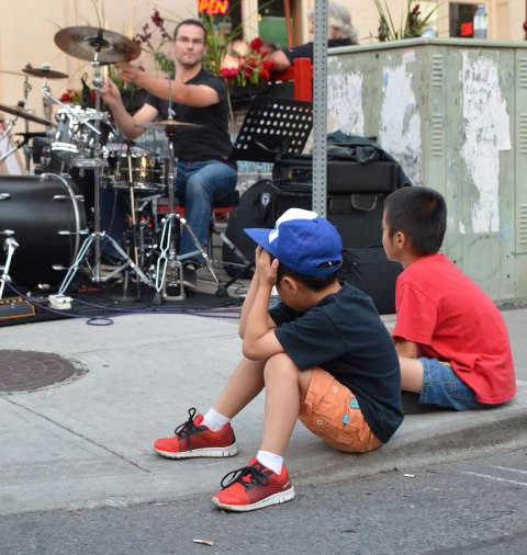 two young boys sitting on the sidewalk watching a drummer play in a band in a street music festival performance