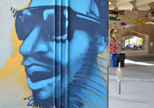 picture of art (mural) on a concrete support holding up a road above a skateboard and basketball park - large blue face of a man wearing sunglasses, in profile, in the foreground.  A pillar with a tall skinny person painted on it in the background.