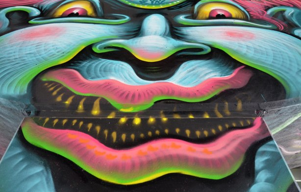 photo of art (mural) on a concrete support holding up a road above a skateboard and basketball park - close up of a multocoloured clown face with a scary expression