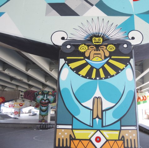 South American themed figure with head dress painted on a pillar, with other painted pillars in the background.
