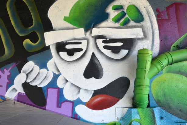 street art painting of a white face, weird eyes and an open mouth