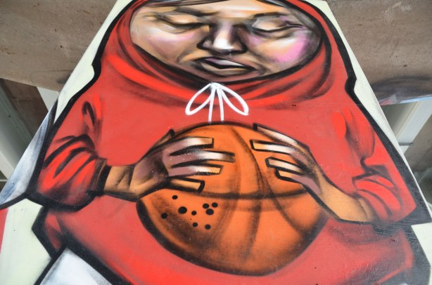 picture of art (mural) on a concrete support holding up a road above a skateboard and basketball park - an elicser painting of a person in a red hoodie holding a basketball.  Eyes closed, thining, hood pulled up over head