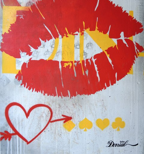 picture of art (mural) on a concrete support holding up a road above a skateboard and basketball park - bottom part of a pillar with a painting of a big red set of lips, a red heart with an arrow through is as well as yellow symbols from playing card - hearts, diamond, spage and club.  Signed Enjoy denial.