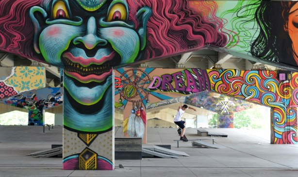 picture of art (mural) on a concrete support holding up a road above a skateboard and basketball park - young man on skateboard jump in the park with many of the pillars in the photo including a large greyish blue clown face
