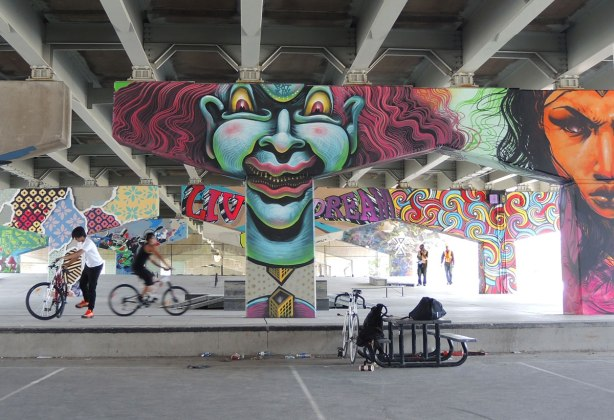 picture of art (mural) on a concrete support holding up a road above a skateboard and basketball park - guys on bikes in the park with many of the pillars in the photo including a large greyish blue clown face and an orange woman's face.