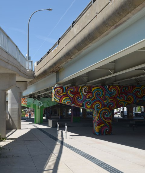 Two overpasses come together to form one, view from below, there is an urban park under the overpass on the right, with the concrete supports holding up the road covered with paintings by street artists.