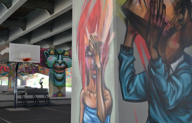 picture of art (mural) on a concrete support holding up a road above a skateboard and basketball park -