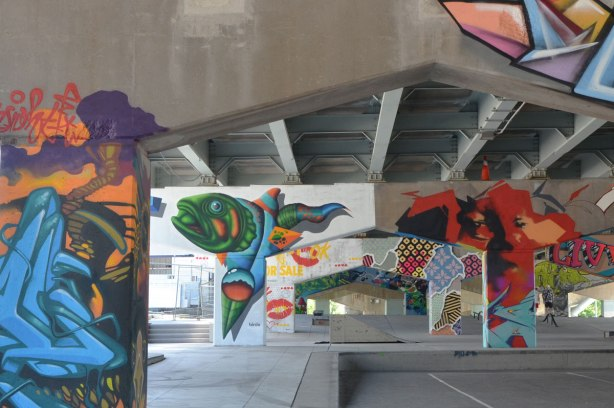 photograph of a number of pillars and supports holding up Eastern Ave as it passes over Lower River St.  Pillars have been painted by street artists including a fish by birdo and lips by Enjoy Denial.   Underpass park.  Toronto