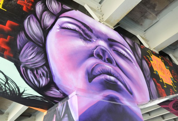 picture of art (mural) on a concrete support holding up a road above a skateboard and basketball park - painting of a large purple woman's face with her eyes closed