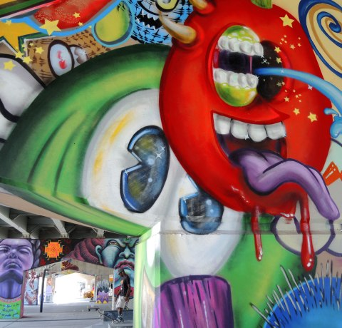 picture of art (mural) on a concrete support holding up a road above a skateboard and basketball park -  lage eyes on one creature, a red creature with open mouth and long purple tonge, by spud, in the foreground.  Other pillars in the background, as well as one young man with a skateboard