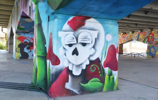 picture of art (mural) on a concrete support holding up a road above a skateboard and basketball park - looking from one corner of the park diagonally through the park.  A creature with a white skull-like face with pinkish red mushrooms in the foreground, other pillars in the background