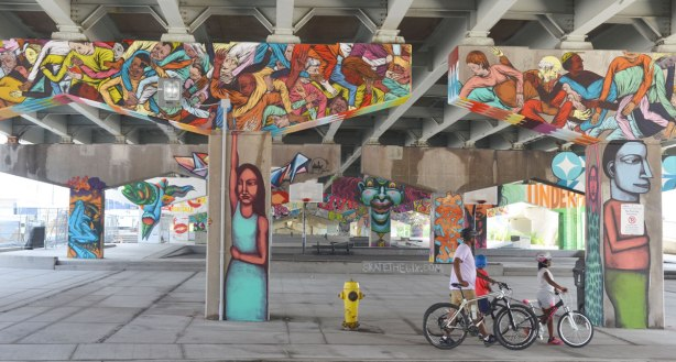 A man and two kids walk their bikes past Underpass Park on Lower River St. in Toronto.  A road is above them.  Concrete supports that hold up that road have been decorated with paintings by various street artists.  Closest to the street, the pillars are people with their arms raised so it looks like they are holding up the road.  The horizontal part of the supprts are covered with pictures of people flying outward from the center.
