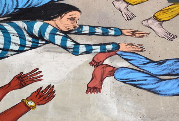 a street artist painting of a woman in a blue and white striped shirt flying with her arms outstretched.  Two pairs of feet as well as a pair of hands belonging to other people are also in the picture.