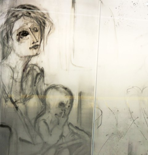 part of an art installation, paintings on glass panels, a woman sitting on the subway with a child on her lap. The child has a finger up its nose