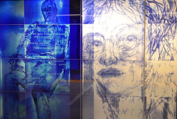 part of an art installation, paintings on glass panels, on the left side is a man on blue and on the right is a woman's head drawn in blue