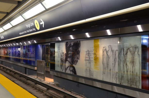 Looking along a subway platform at Union Station, the far wall is an art installation, paintings on glass panels of people