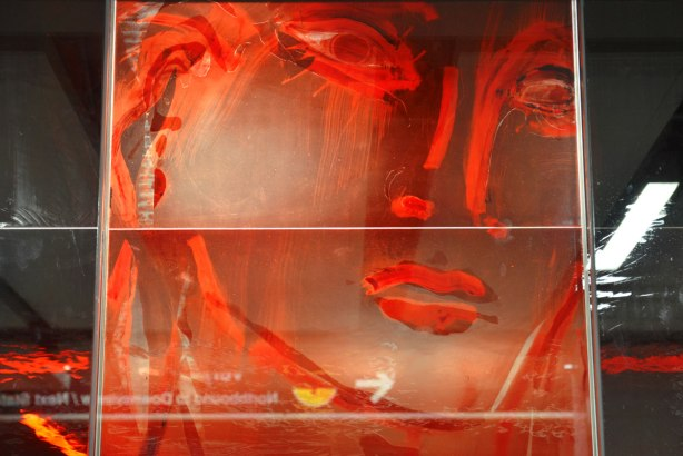part of an art installation, paintings on glass panels, a large face in red