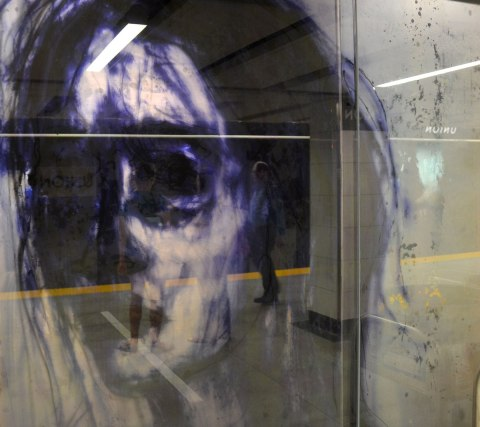 part of an art installation, paintings on glass panels, a woman's head in dark blues and blacks, heavy paint around the eyes