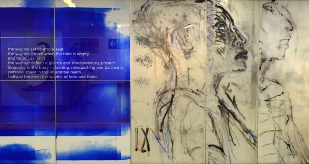 part of an art installation, paintings on glass panels, on the left are white words on blue background, on the right are two women in profile