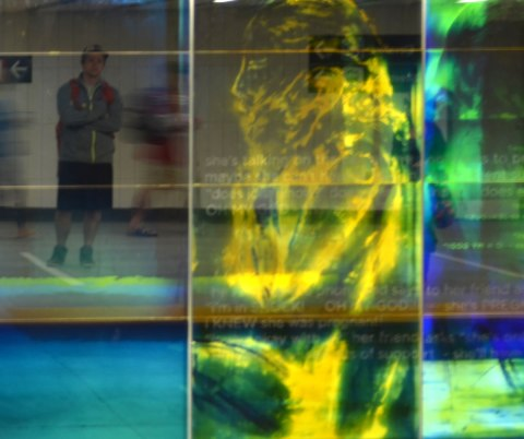 part of an art installation, paintings on glass panels, a woman in yellow on a green and blue background, a man is waiting for the subway and his reflection is in the photo