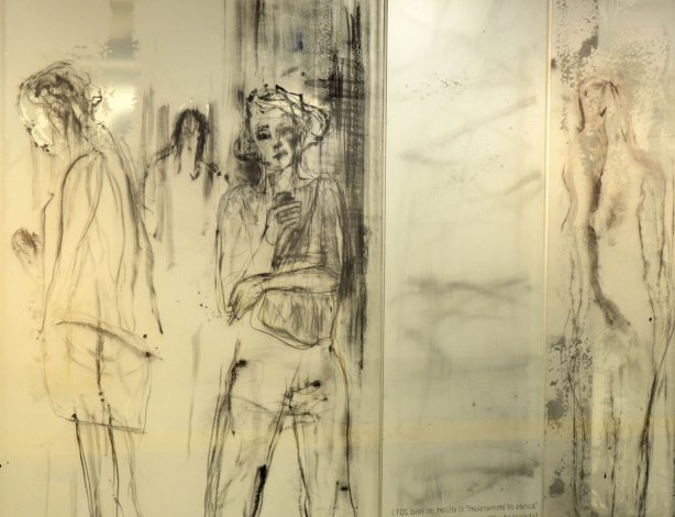 part of an art installation, paintings on glass panels, woman standining