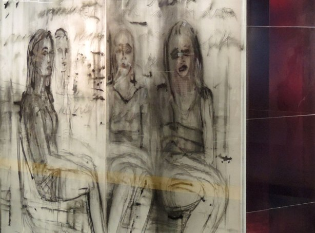 part of an art installation, paintings on glass panels, four women sitting on the subway