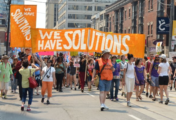 Marchers on the jobs, justice and climate action protest march who are carrying a large orange banner that says We have solutions.
