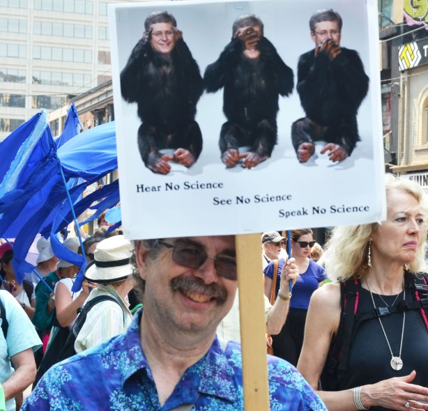 A man is holding up a protest sign with Prime Minister Stephen Harper's head on three monkeys along with the worsd, Hear no science, speak no science, see no science.