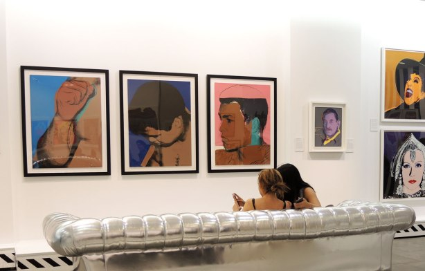Two women are sitting ona silver couch in an art gallery.  On the wall in front of them are 3 silkscreen Andy Warhol prints of Mohammad Ali.