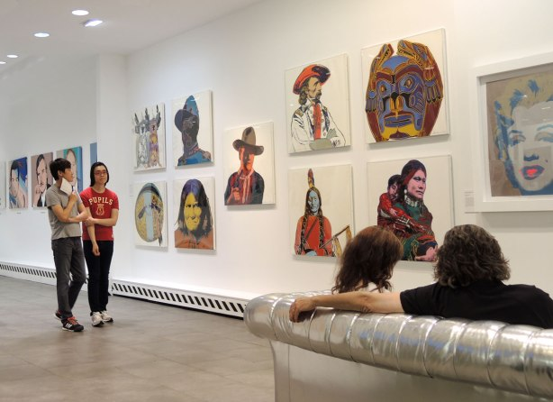 Some of Warhol's Cowboys and Indians series prints hang on a gallery wall as two young Asian men walk past. There is also a couple sitting on a silver coloured couch in the right side of the photo.