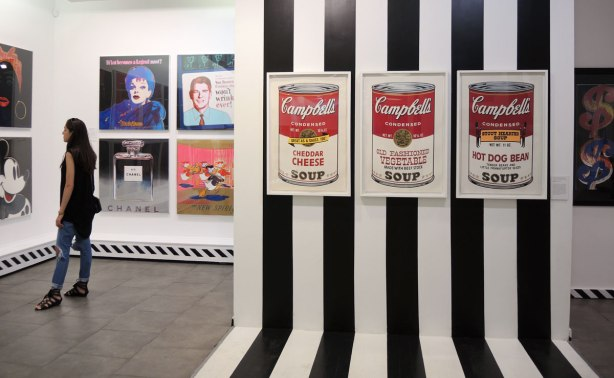 prints of three Campbells soup cans on a black and white striped wall, cheddar cheese, old fashioned vegetable, and hot dog bean.  To the left a woman is looking at other Andy Warhol prints on a wall including a print of Mickey Mouse, Lucille Ball and a young Ronald Regan.