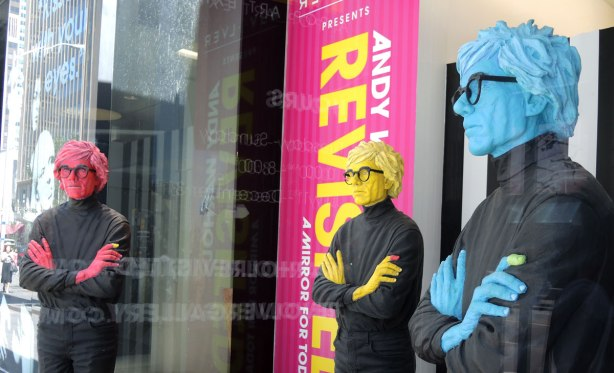 statues of Andy Warhol, one pink, one yellow and one blue, in a window of an art gallery,  He's dressed in black, with black rimmed glasses and his hands are folded over his chest in all three statues.  Life sized.