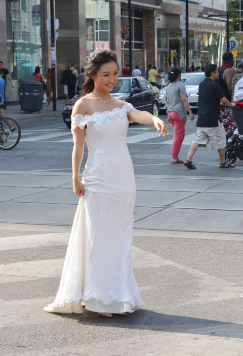 A bride is standing in the middle of an intersection in downtown Toronto, wearing a long white wedding dress, she has her arm up and is beckoning to the groom.