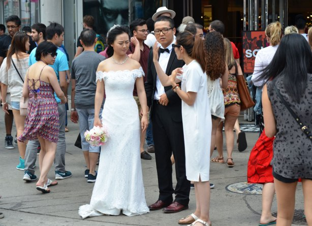 A bride and groom are standing on the corner of Yonge and Dundas streets in Toronto.  They are talking to a woman in a white dress who is organizing the wedding photo shoot.