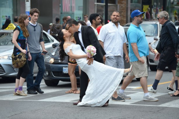 The bridegroom in his black suit dips the bride in her white wedding dress in the middle of a pedestrian crossing across Yonge St. at Dundas in TOronto.