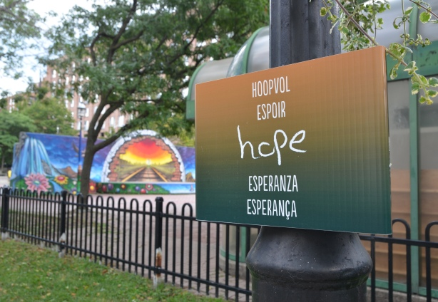 sign on a lamp post that says hope in 5 languages with a basketball court and murals in the background. On the Esplanade in Toronto