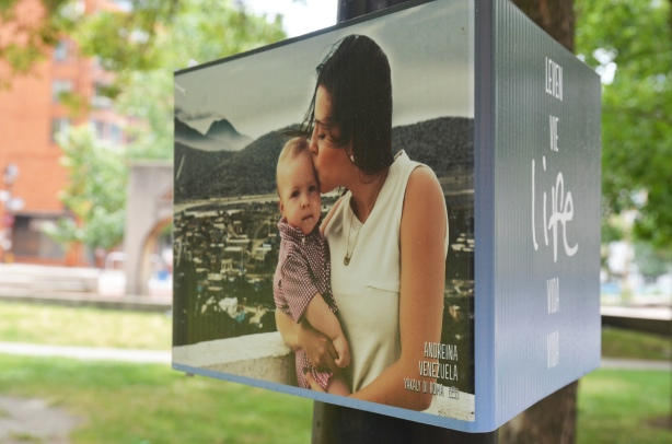 poster on a lamp post with the picture of a mother and her son. Park is in the background. Part of an exhibit in association with the Pan Am Games.