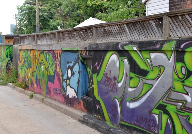 a fence that runs down the right side of an alley has been covered with street art