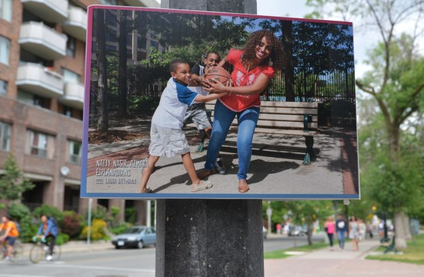 A poster on a lamp pole, a picture of a woman and two boys playing with a ball (pretending to fight over it)