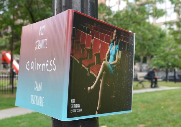 An exhibit on a street in Toronto that consists of a three sided sign wrapped around a streetlight pole. Two sides can be seen in this photo. One side is a picture of a woman sitting in an otherwise empty auditorium with red seats. the other side has the word calmness in English and then the translation of that in 4 other languages, French, SPanish, Dutch and Portugese