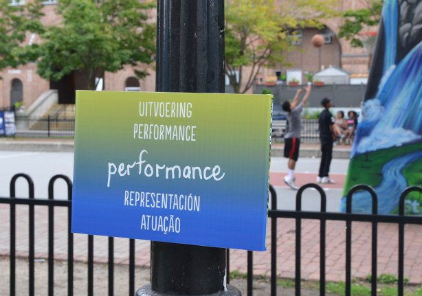 The word performance on a green and blue sign. It is also written in 4 other languages, Dutch, Spanish, French and Portugese