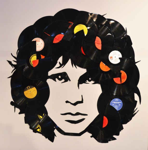 image of Jim Morrison, the guitar player from Doors, his head with facial features painted in black but his hair is made with broken records.