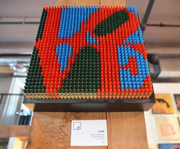 An image of the famous LOVE red letters in a black and blue square, this one is made of red, black and blue crayons on end.
