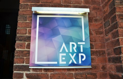 Gallery sign on the exterior of a brick building, square sign with purplish background.  Art Exp is the name of the gallery
