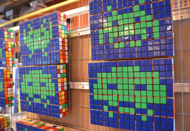 Little green space invaders from the old video game made of Rubiks cubes, green space invaders on blue background.
